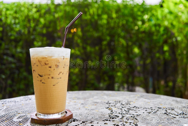 Café congelado na tabela branca com fundo verde do jardim foto de stock
