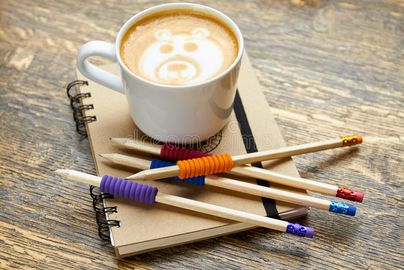 Café, cuaderno y lápices fotografía de archivo