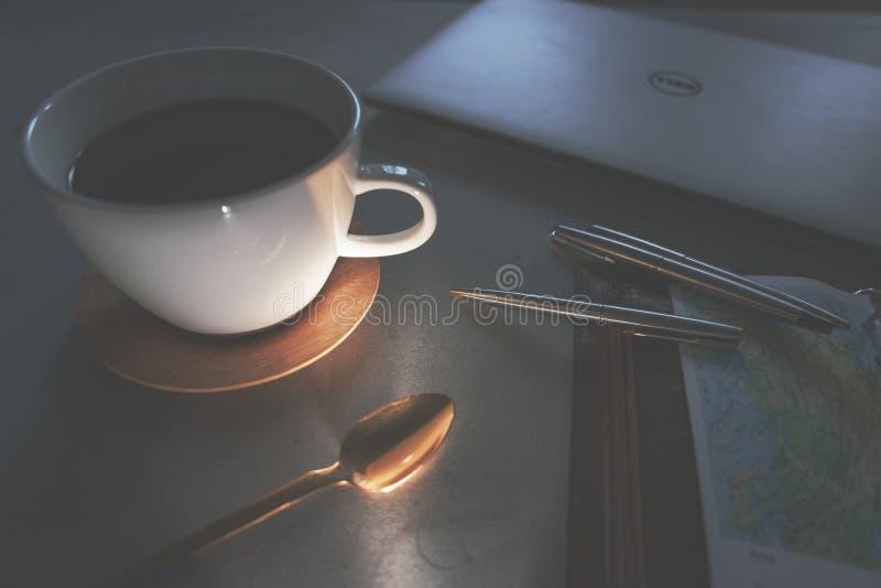 Café, cuchara, mapa del viaje del ordenador portátil y plumas en la tabla concreta en la tarde foto de archivo