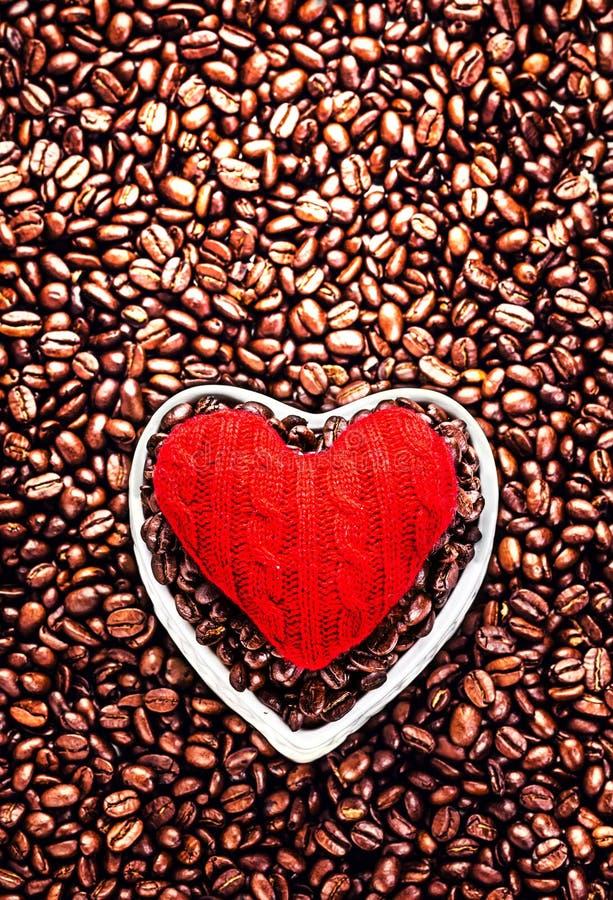 Café d'amour à la Saint-Valentin. Grains de café rôtis avec le rouge il image libre de droits