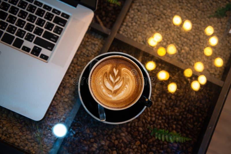 Café d'art d'Atte dans la tasse noire avec l'ordinateur portable et le bokeh des lumières sur la table photographie stock