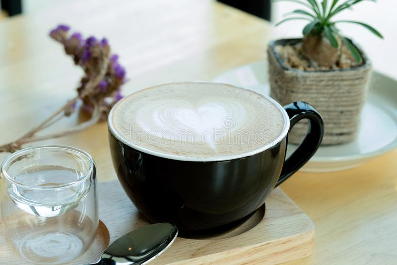 Café d'art de Latte dans le temps de matin avec la lumière du soleil sur le fond en bois de table au café images libres de droits