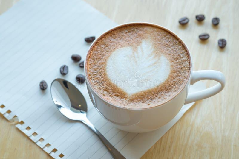 Café d'art de Latte et grains de café rôtis sur le backg en bois de table photographie stock