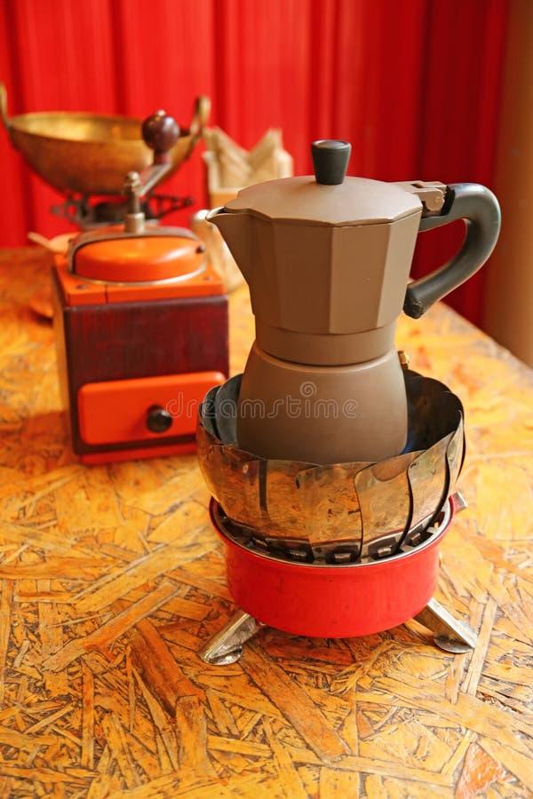 Café d'expresso étant brassé dans un pot de Moka avec une rétro broyeur de café en bois à l'arrière-plan photographie stock libre de droits