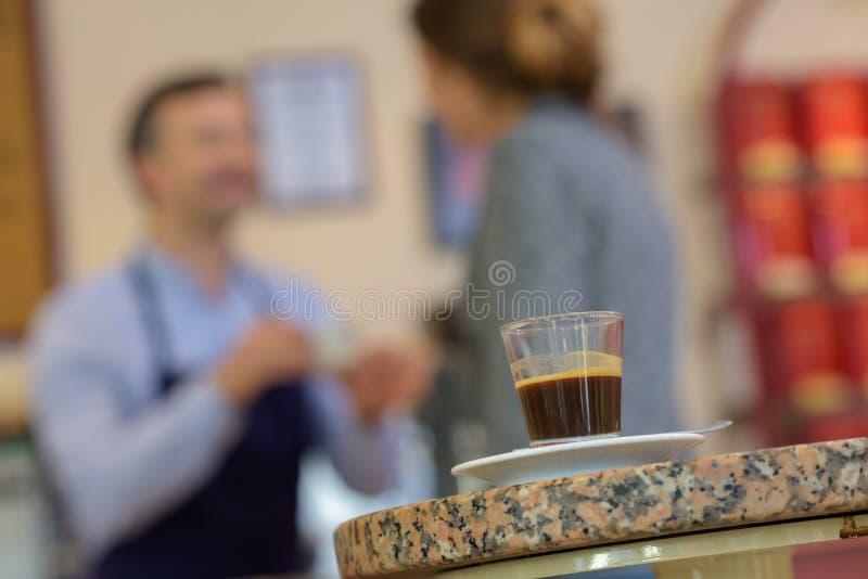 Café d'expresso dans des personnes de premier plan derrière image stock