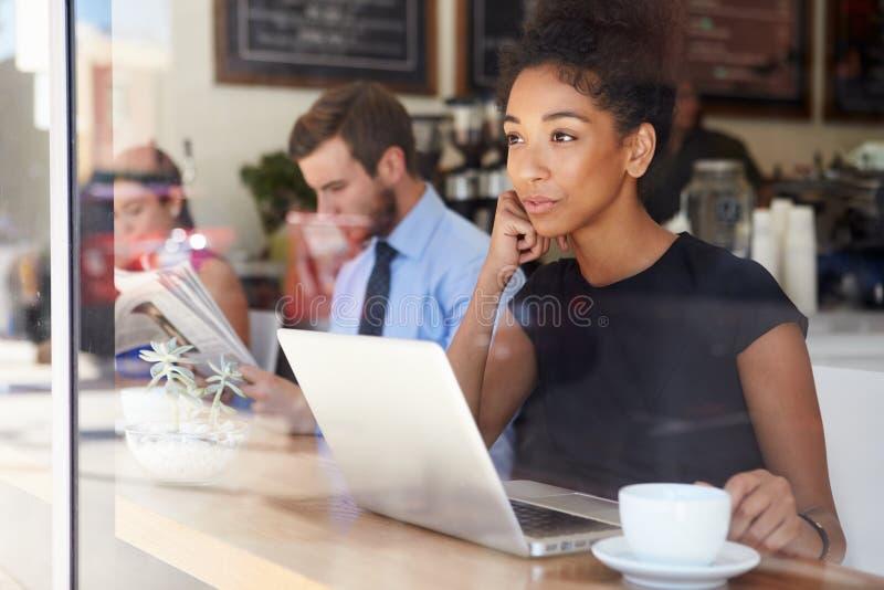 Café d'Using Laptop In de femme d'affaires photos stock