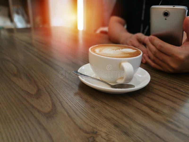 Café da arte do Latte no fundo da tabela e no usi de madeira do homem imagens de stock royalty free