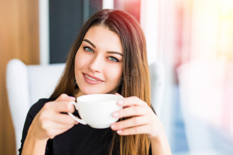 Café da jovem mulher bonita ou chá e olhar bebendo na câmera imagem de stock royalty free