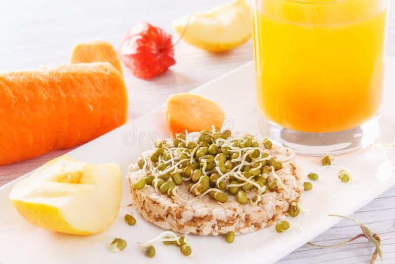 Café da manhã útil dos produtos naturais Grões brotadas em um bolo soprado do trigo Maçãs e cenouras frescas, suco fresco imagem de stock
