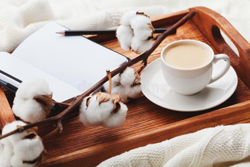 Café da manhã acolhedor com xícara de café, flor do algodão e o caderno aberto na bandeja de madeira rústica na cama imagens de stock