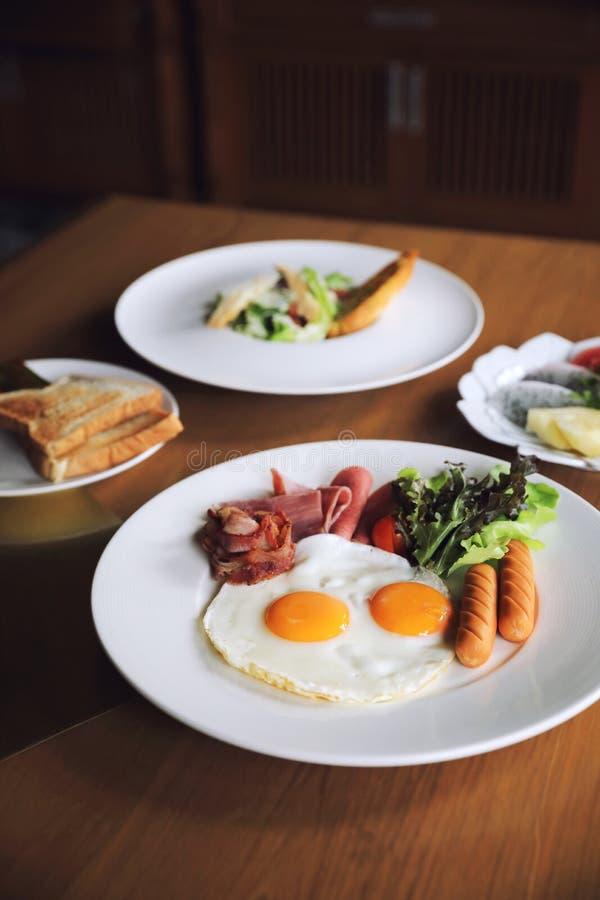 Café da manhã ajustado com ovos fritos, bacon, salsichas, feijões, brindes, salada fresca e fruto na tabela de madeira fotos de stock