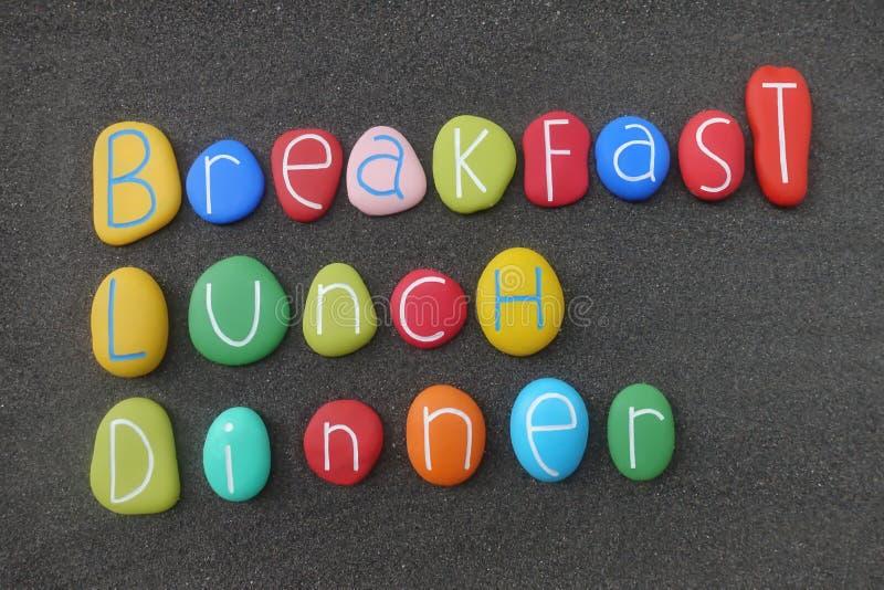 Café da manhã, almoço, texto do jantar composto com as pedras coloridas sobre a areia vulcânica preta foto de stock