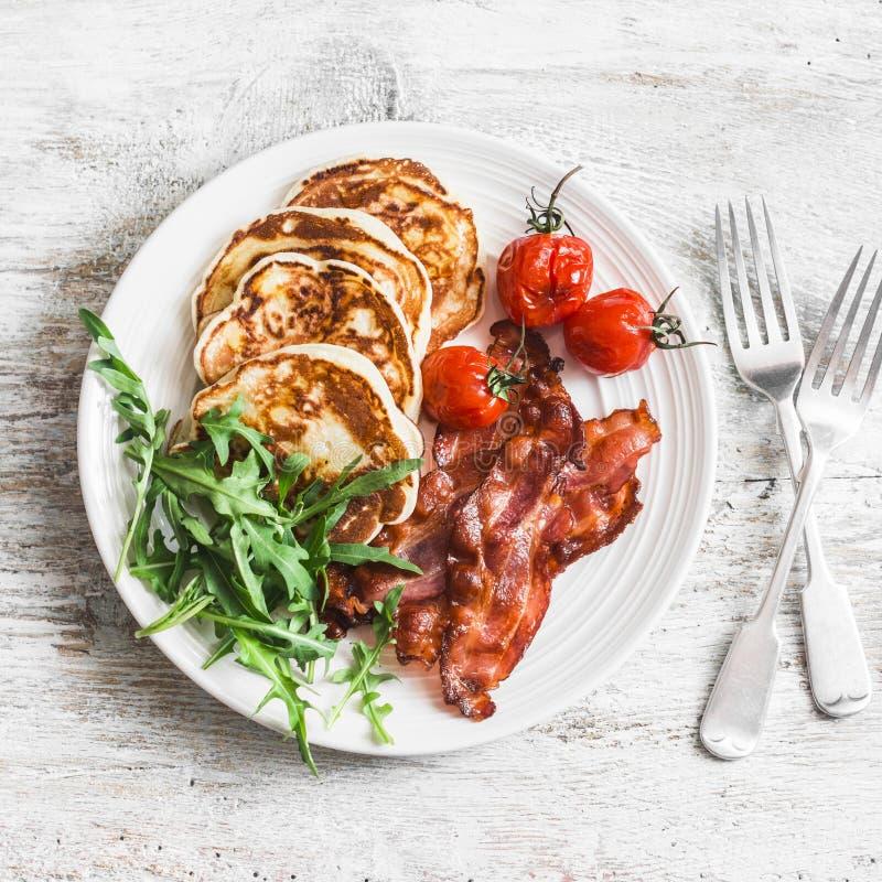 Café da manhã americano tradicional - o bacon friável, panquecas com xarope de bordo, roasted tomates, rúcula Em um fundo claro imagem de stock