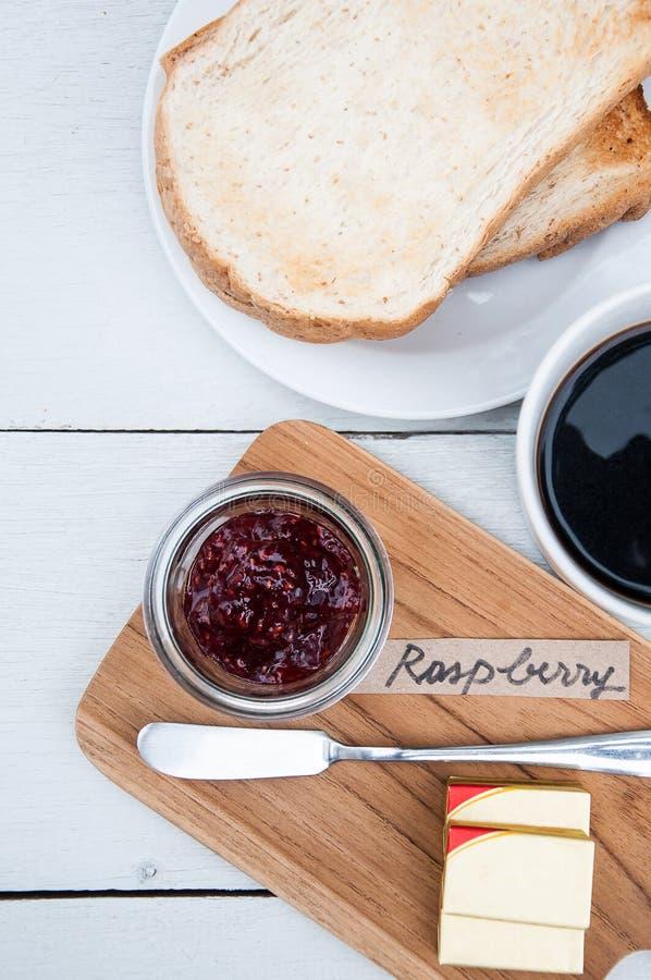 Café da manhã: brindes, manteiga, doce de framboesa, copo do café preto imagem de stock