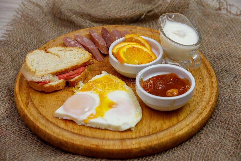 Café da manhã caseiro natural dos ovos mexidos, brinde, salsichas da caça e doce, apresentados em uma placa de madeira O conceito imagem de stock royalty free