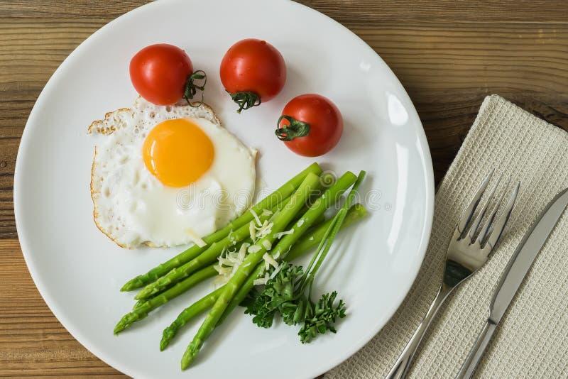 Café da manhã caseiro saudável com ovos fritos e aspargo fresco no close-up da placa, servido com tomates Vista superior fotos de stock royalty free