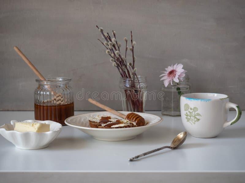 Café da manhã claro de brindes do centeio-pão com cereais com manteiga e mel Chá em uma caneca cerâmica imagem de stock royalty free