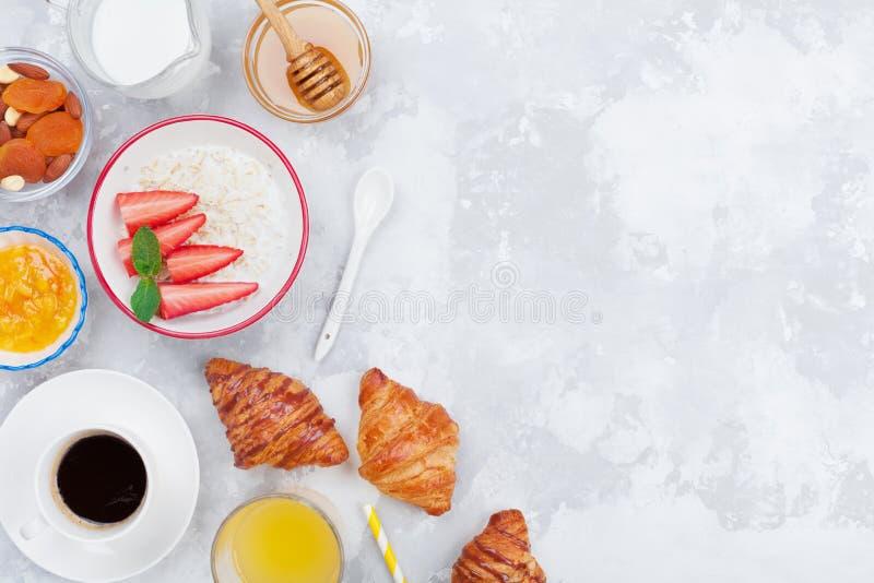 Café da manhã da manhã com café, croissant, farinha de aveia, doce, mel e suco na opinião de tampo da mesa de pedra Sspace para o fotografia de stock royalty free