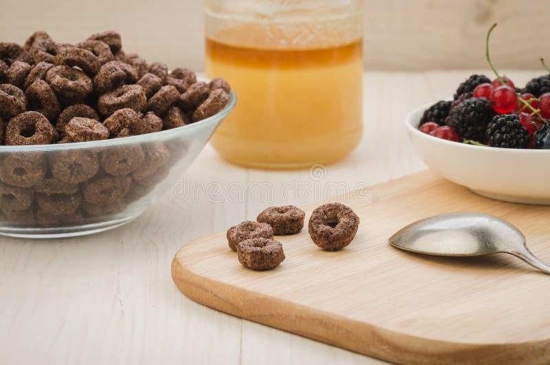 café da manhã com flocos, bagas, mel/café da manhã com flocos, bagas, mel em uma bandeja de madeira Foco seletivo imagem de stock