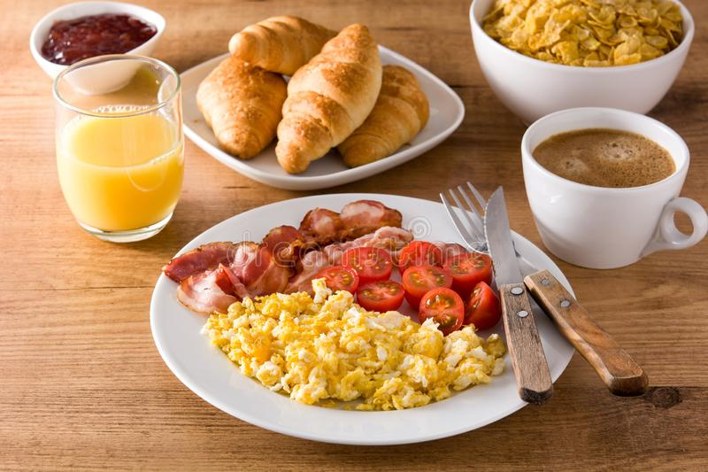 Café da manhã com os flocos dos ovos mexidos, do bacon, dos tomates, do café, do suco de laranja, do croissant e de milho fotos de stock royalty free
