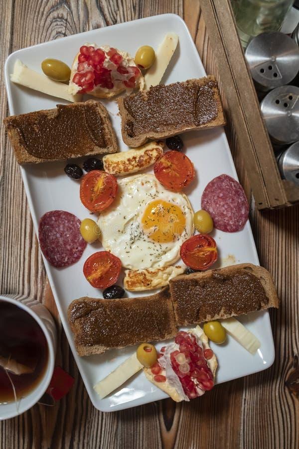Café da manhã com ovo frito, pão de centeio, romã, pasta da alfarroba, queijos, azeitonas, salame seco, tomates e chá imagem de stock royalty free