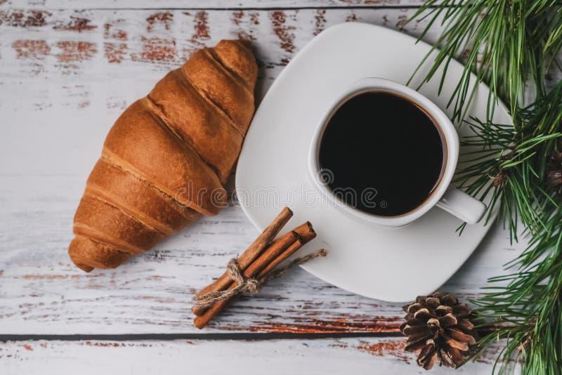Café da manhã com uma xícara de café, croissant do Natal da manhã, varas de canela foto de stock royalty free