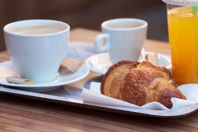café da manhã com xícara de café, o croissant francês e o suco de laranja no fundo de madeira da tabela fotos de stock