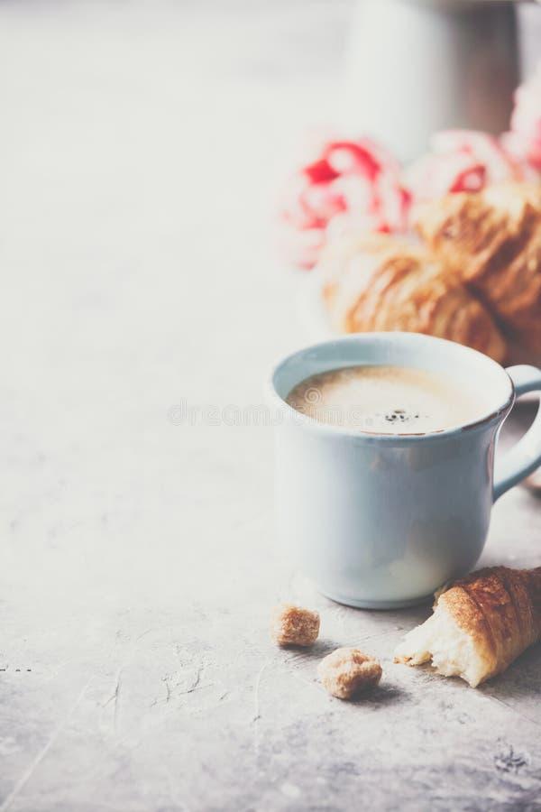 Café da manhã, croissant e tulipas da mola em claro - fundo cinzento fotografia de stock