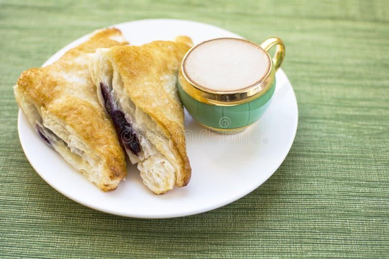 Café da manhã da massa folhada do sapateiro do cappuccino e do mirtilo foto de stock