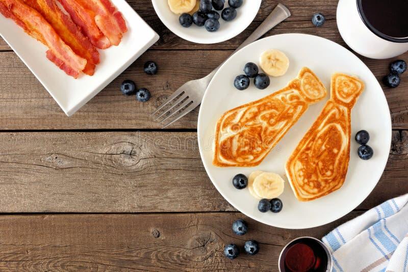 Café da manhã dado forma laço da panqueca do dia de pais, beira do canto da vista superior em um fundo de madeira rústico foto de stock