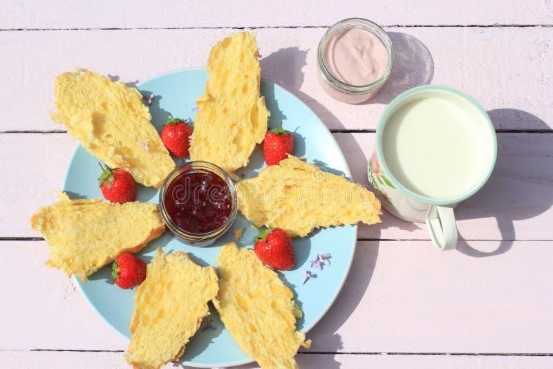 Café da manhã delicioso com croissant, as morangos, leite e iogurte frescos no fundo de madeira velho, foto de stock royalty free