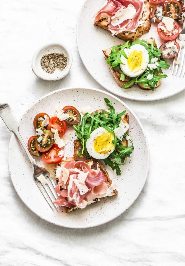 Café da manhã delicioso, petisco, aperitivos para o vinho, tapas - sanduíches com prosciutto, ovo, rúcula, tomates de cereja e ch imagens de stock