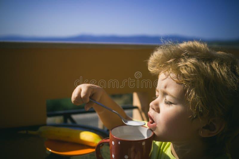 Café da manhã desagradável Uma criança come um batido de leite num terraço de um apartamento perto do mar imagem de stock