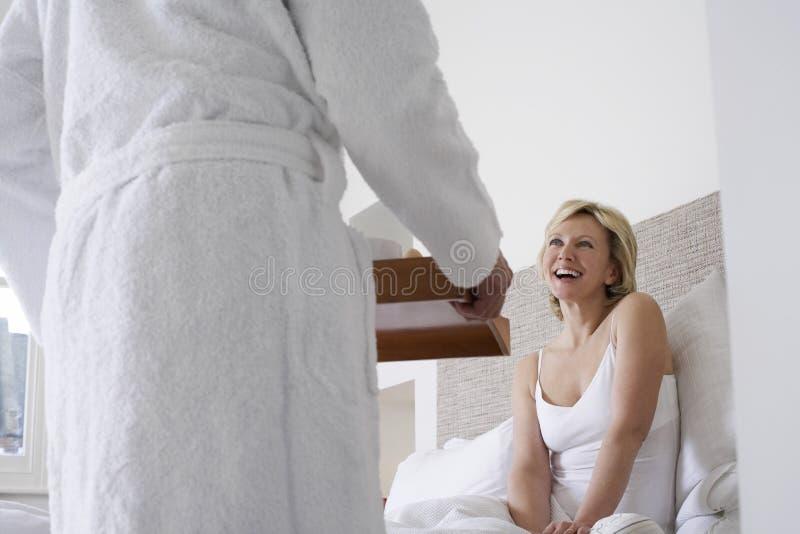 Café da manhã do serviço do homem à mulher alegre na cama fotos de stock royalty free