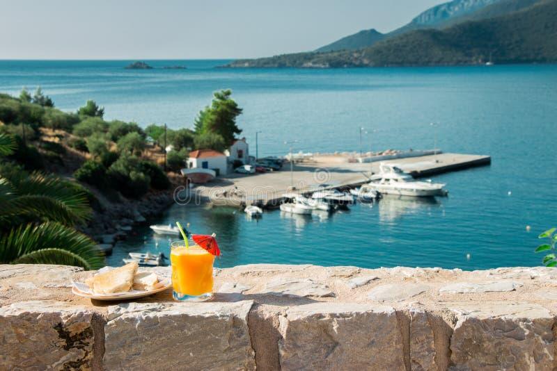 Café da manhã do suco de laranja e do brinde com opiniões do mar foto de stock