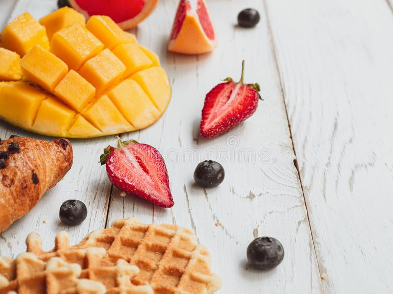 Café da manhã do verão com waffle e frutos frescos Fatias de manga, de morango, e de uma cereja no fundo de madeira imagem de stock