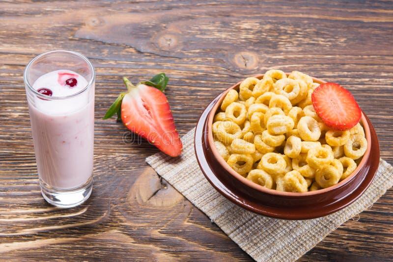 Café da manhã dos cereais e do iogurte, em uma tabela de madeira, e morangos maduras foto de stock royalty free