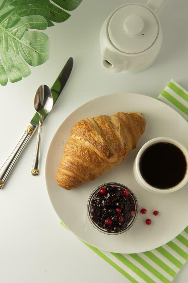 Café da manhã, café e croissant com doce da baga na tabela branca Croissant francês Bolos frescos refeição, petisco Isoalted com  imagens de stock royalty free