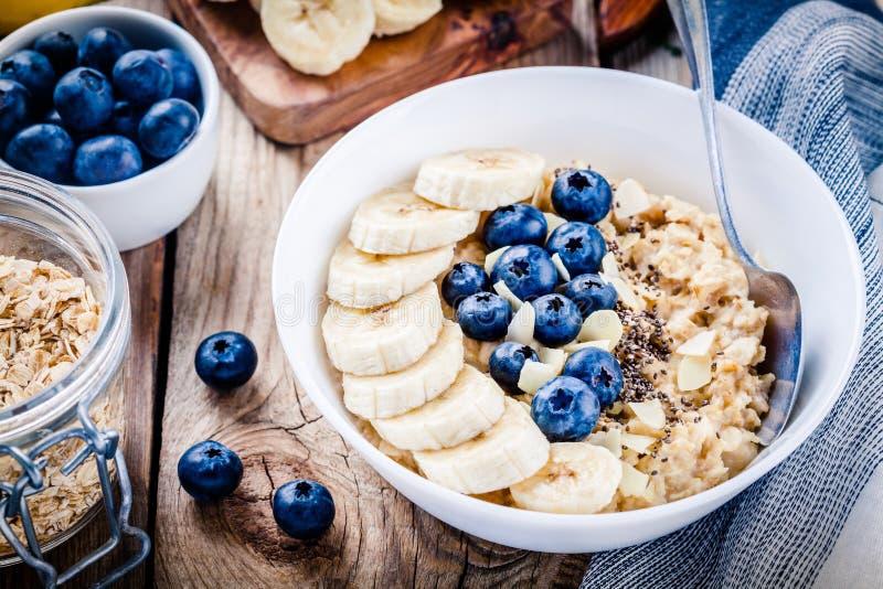 Café da manhã: farinha de aveia com bananas, mirtilos, sementes do chia e amêndoas fotografia de stock royalty free