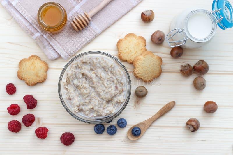 Café da manhã da farinha de aveia com mirtilos, framboesas, cookies, mel, leite e avelã imagens de stock royalty free