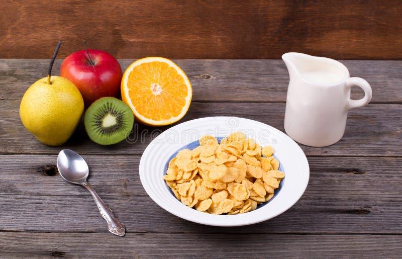 Café da manhã: flocos em uma placa, leite em um jarro fotografia de stock royalty free