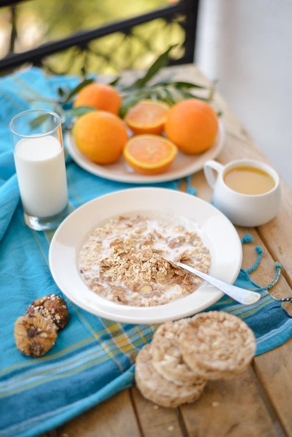 Café da manhã, fruto, flocos de milho, leite e suco de laranja na tabela de madeira imagens de stock