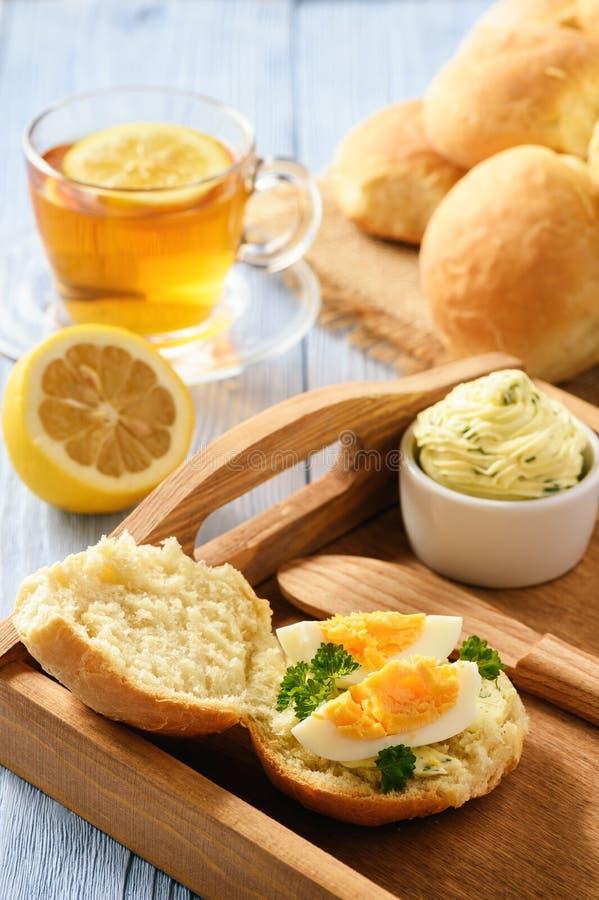 Café da manhã home - rolos de pão caseiro, copo do chá, ovos cozidos e manteiga de erva do alho imagem de stock royalty free