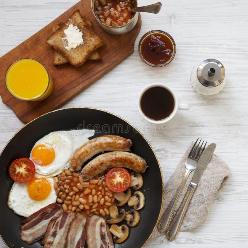 Caf? da manh? ingl?s completo em uma bandeja com ovos fritos, bacon, feij?es, salsichas e brindes na superf?cie de madeira branca imagens de stock