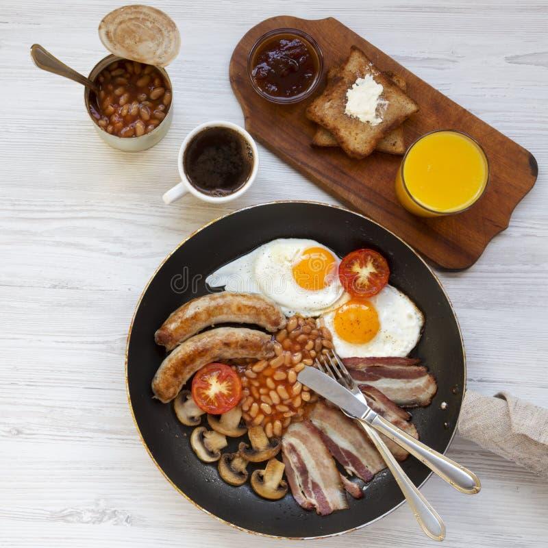Café da manhã inglês completo em uma bandeja com ovos fritos, bacon, salsichas, feijões e brindes na tabela de madeira branca, vi fotografia de stock royalty free