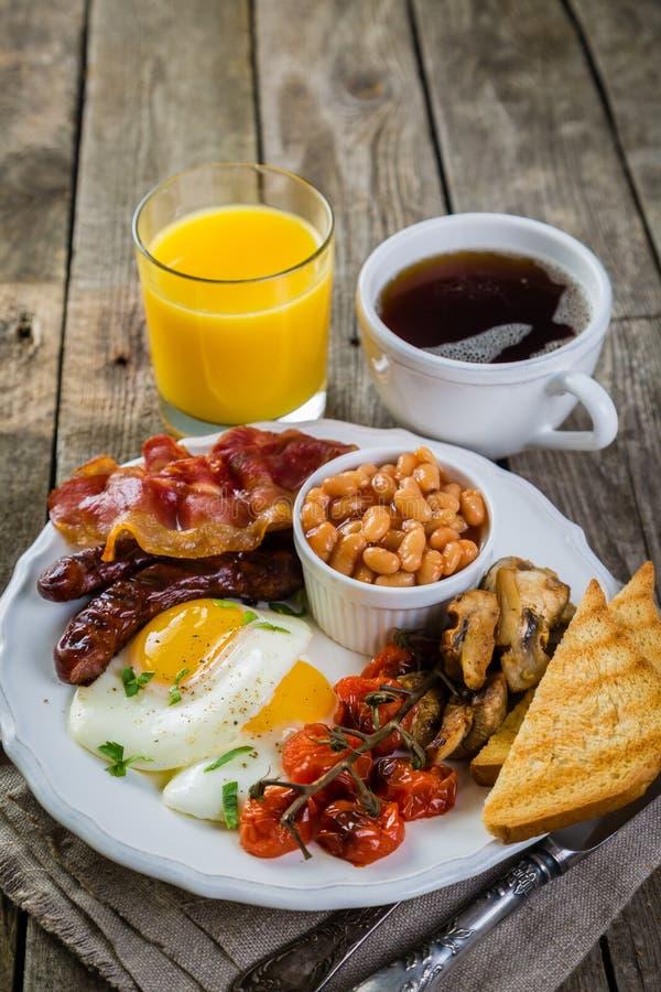 Café da manhã inglês completo - ovos, bacon, feijões, brinde, café e suco imagem de stock