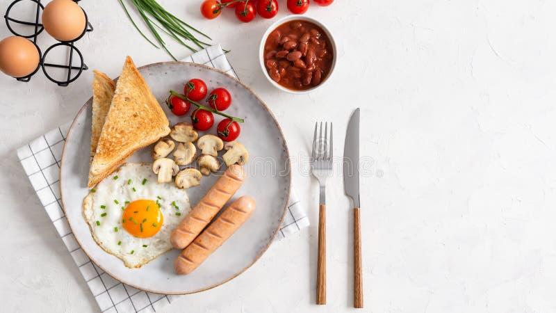 Caf? da manh? ingl?s completo que inclui salsichas, tomates e cogumelos grelhados, ovo, feij?es cozidos e p?o Vista superior, esp fotos de stock