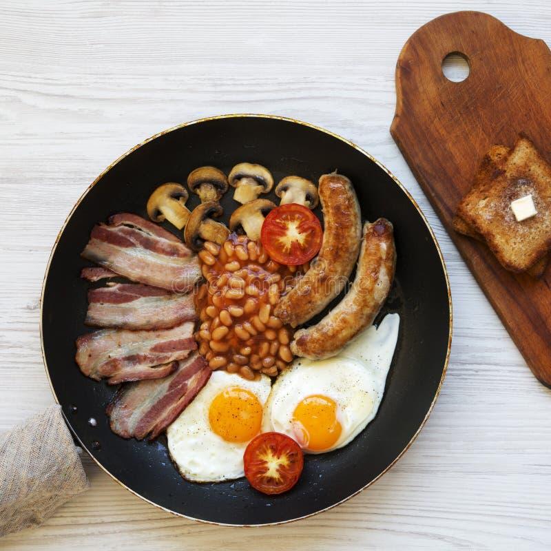 Café da manhã inglês em uma bandeja com ovos fritos, bacon, feijões, salsichas e brindes em uma superfície de madeira branca, vis foto de stock