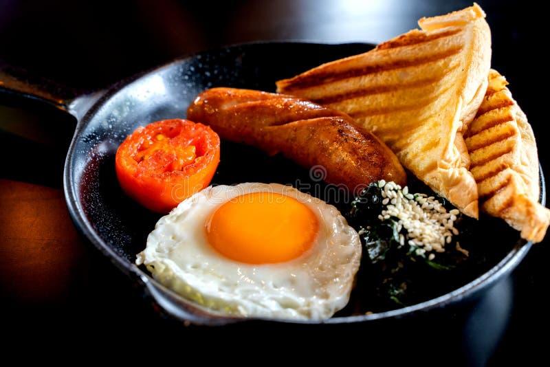 Café da manhã inglês: ovo frito, bacon, salsicha e brinde na bandeja imagens de stock