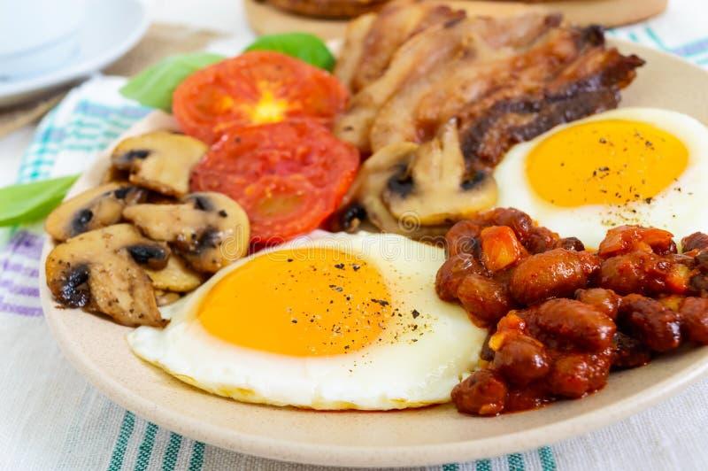 Café da manhã inglês: ovos, bacon, feijões no molho de tomate, cogumelos, tomates, brinde com queijo creme e uma xícara de café imagem de stock royalty free